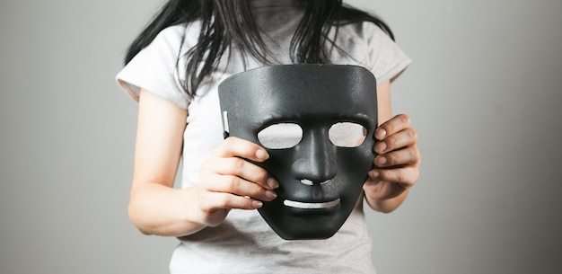 Woman holding black anonymous mask