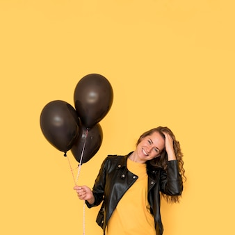 Woman holding black balloons front view