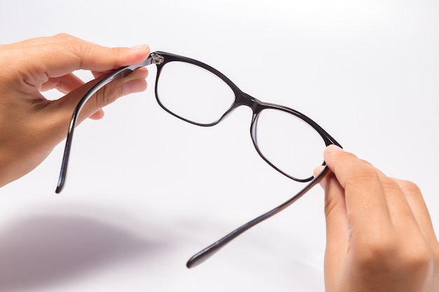 Woman holding the black eye glasses spectacles with shiny black frame isolated on white