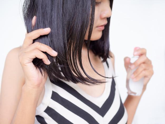 黒髪とビタミンe入りのオイルをボトルに入れて脱毛を防ぎ、ざらざらした滑らかな柔らかさの女性。本物のスリムフィットと肌日焼けアジアタイ。健康的で美しいコンセプトの化粧品。