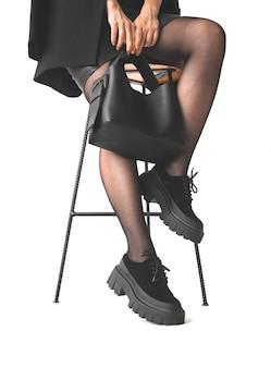 椅子に座っている間、白い背景、ショッピング、実業家のコンセプト写真で隔離の黒い革のハンドバッグを保持している女性