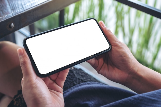 A woman holding black mobile phone with blank desktop screen while sitting in cafe