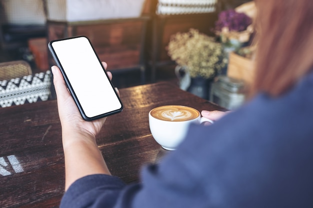 A woman holding black mobile phone with blank screen while drinking coffee in vintage cafe
