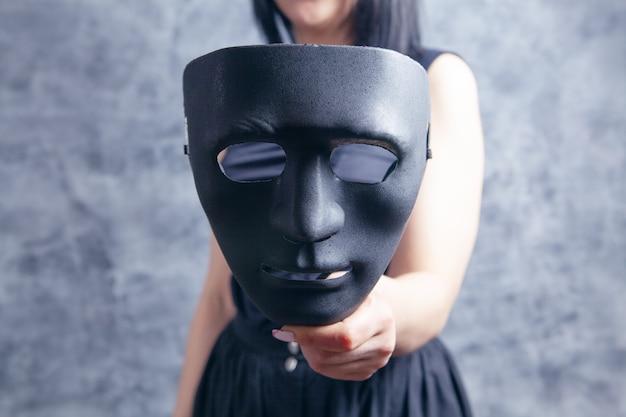 Woman holding black plastic mask on gray background