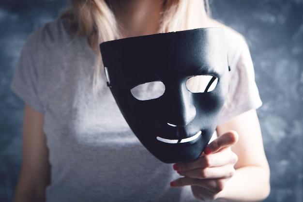 Woman holding black plastic mask on gray