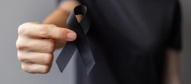 Женщина, держащая черную ленту для меланомы и рака кожи, месяц осведомленности о травмах от вакцины, горе и покой с миром. здравоохранение и расистская концепция