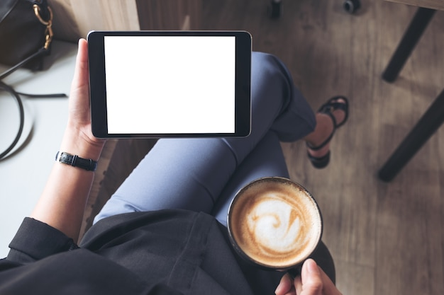 Woman holding black tablet pc with blank desktop screen while drinking coffee