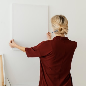Woman holding a blank canvas