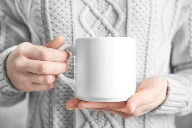 Woman holding blank cup for branding in hands