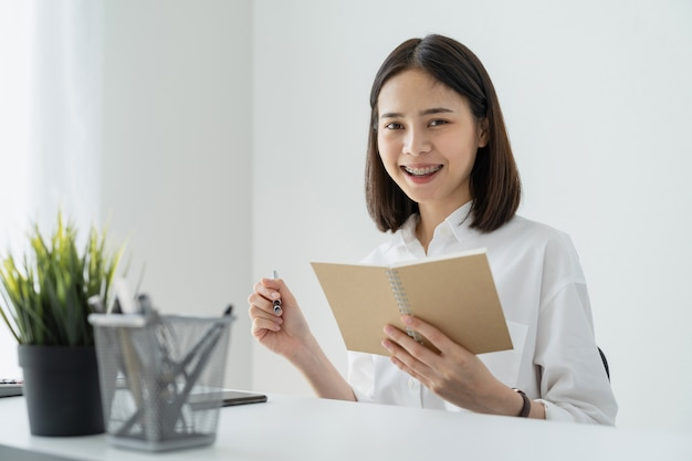Woman holding blank notebook and pen on table in office.