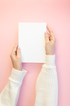 Woman holding blank paper sheet