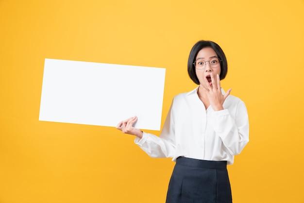 笑顔で白紙を保持し、オレンジを見ている女性。
