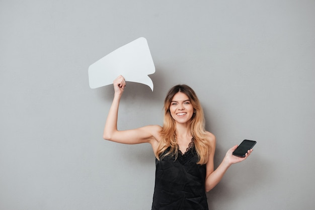 Woman holding blank screen mobile phone and speech bubble