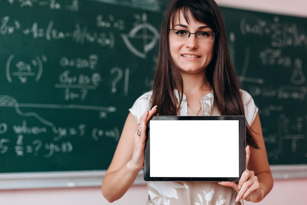 Woman holding a blank screen white mockup in her hands and looking at the camera