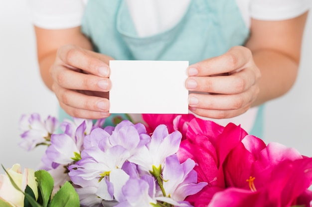 Woman holding blank visiting card over fresh flowers