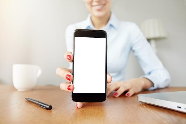 Donna che tiene lo schermo bianco vuoto dello smartphone