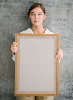 Woman holding a blank wooden photo frame