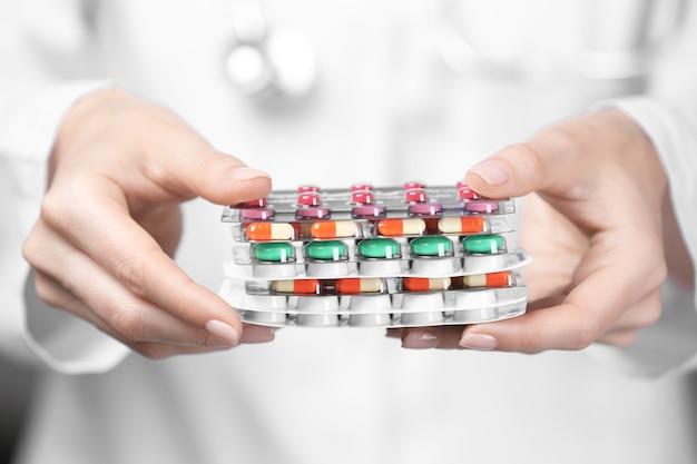 Женщина, держащая волдыри с таблетками, крупным планом