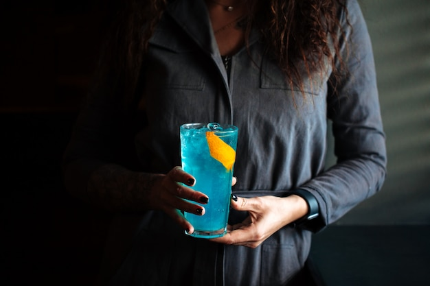Woman holding blue cocktail in a highball with ice