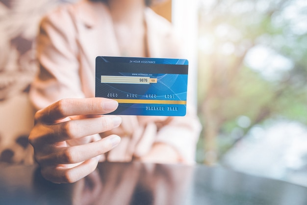 Woman holding a blue credit card to make purchases.
