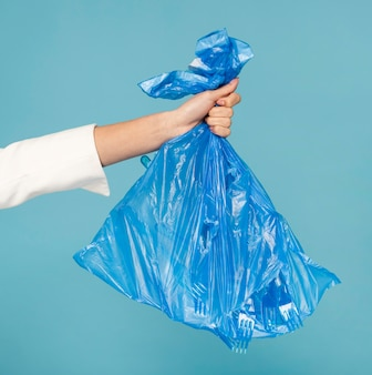 Woman holding a blue plastic trash bag
