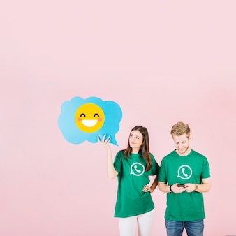 Woman holding blue speech bubble with laughing emoji near man using cellphone