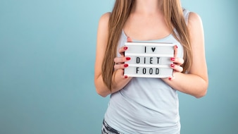 Woman holding board with I love diet food inscription