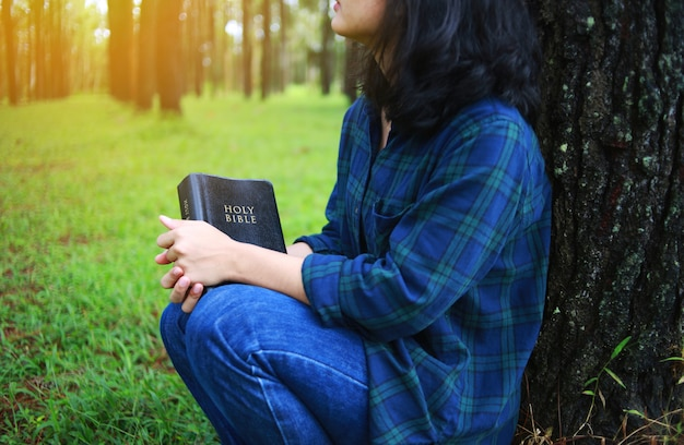 Woman holding a book, the bible, nature.