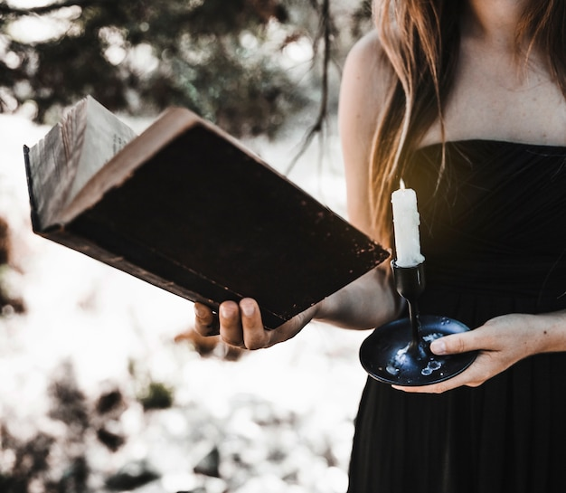 Woman holding book and candle in forest