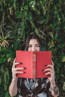Woman holding book in front of her mouth standing against plant