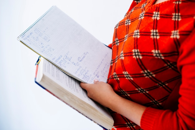 Woman holding book and notebook in studio
