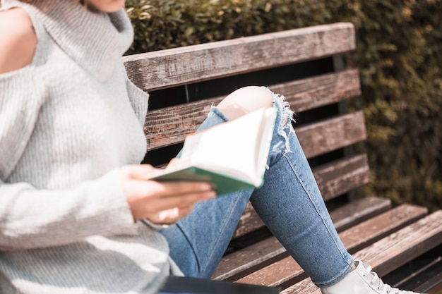 Woman holding book and sitting on bench