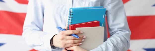 Женщина держит книги и ручку на фоне флага великобритании, изучающего английский язык