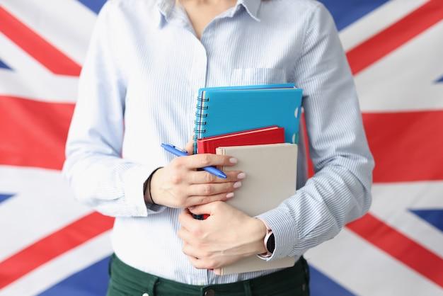 英国の旗を背景に本とペンを保持している女性