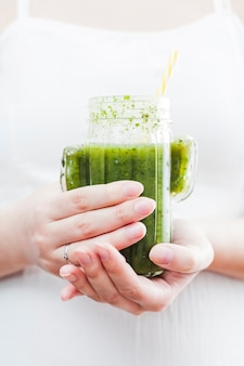 Woman holding bottle of green smoothie