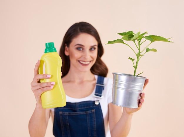 化学肥料と苗のボトルを保持している女性