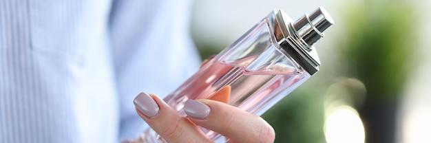 彼女の手のクローズアップで香水のボトルを保持している女性。アロマテラピーのコンセプト