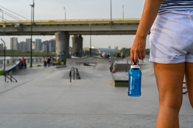 Woman holding a bottle of water after riding in an extreme park. the skate park, rollerdrome, quarter and half pipe ramps. extreme sport, youth urban culture for teen street activity.
