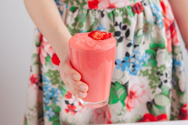 Woman holding bottle with delicious smoothie close up