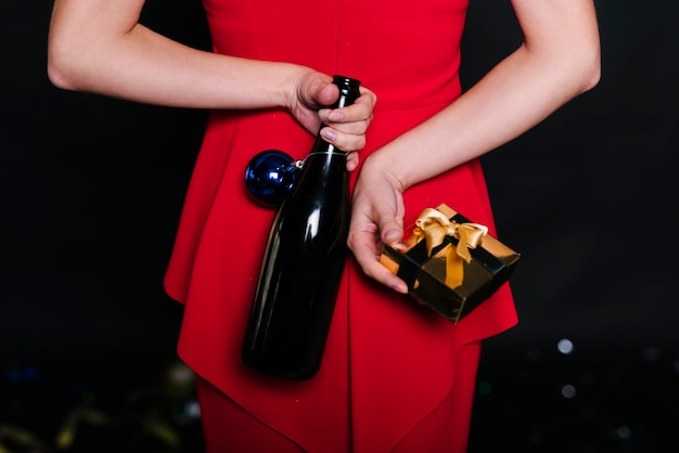 Woman holding bottle with gift box behind back