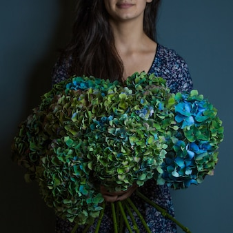 A woman holding a bouquet of decorative green and blue leaf flowers in the hand on room wall