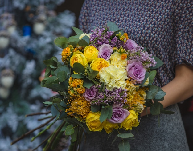 A woman holding a bouquet of fall autumn color flowers in the hand