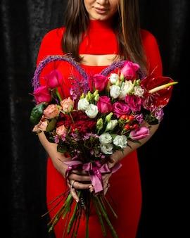 アンスリウムの花dahliwhiteと赤いバラの花束を保持している女性