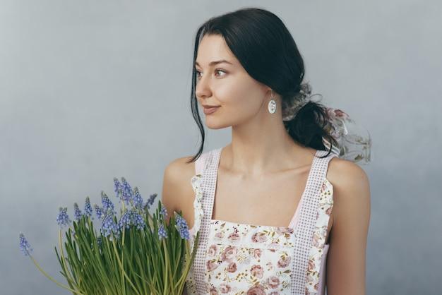Женщина держит букет цветов в руках на сером фоне
