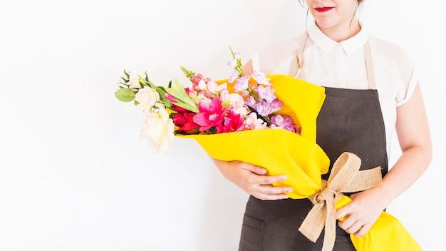 白い背景に花の花束を持っている女性