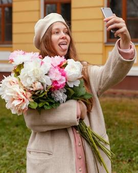 Женщина держит букет цветов на открытом воздухе весной и делает селфи