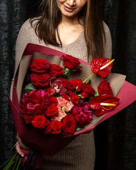 ピンクと赤のバラのアンスリウムと牡丹の花の花束を保持している女性