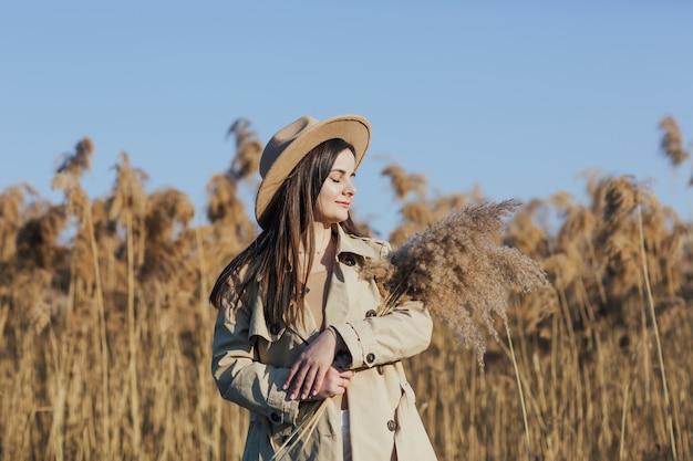 葦の花束を持っている女性