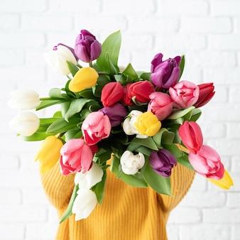 여자가 그녀의 얼굴 앞에서 튤립 꽃다발을 들고