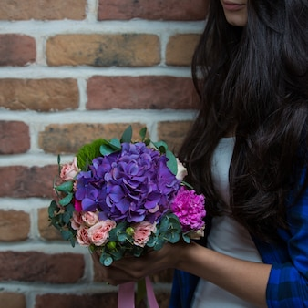 A woman holding a bouquet of purple flowers in the hand